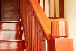 Newel post of wooden stairs in red brown shade of Makha wood or Rosewood in contemporary style ,top view from upstairs , selective focus on newel post