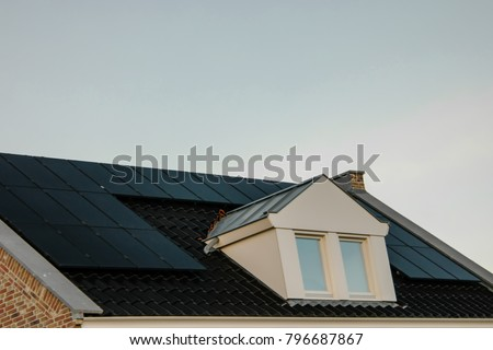 Newly build houses in the Netherlands with solar panels attached on the roof against a sunny sky Close up of new building  black solar panels.Zonnepanelen Translation: Solar  panel, Sun energy #796687867