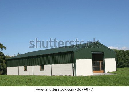 Newly constructed barn of cream painted concrete block walls with a green metal sheet roof,set against a blue sky and trees to the rear.