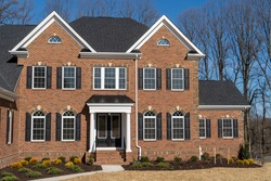 Newly constructed mansion style estate home with curb appeal landscaping, brick facade, double peak gable, symmetric arched windows with shutter, portico  covered with metal hip roof, round columns