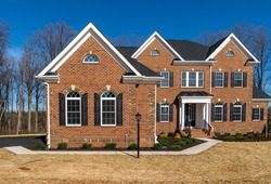 Newly constructed mansion style estate home with curb appeal landscaping, brick facade, triple peak gable, symmetric arched windows with shutter, portico covered w/ metal hip roof, Quoin brick corner