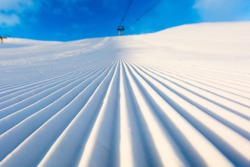 Newly groomed snow on ski slope at ski resort on a sunny winter day.