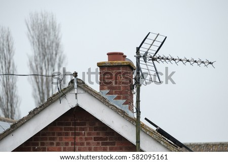 Newly installed home TV antenna seen attached to a large bungalow's apex roof, which also shows a hooked up telephone cable. #582095161