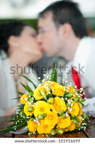 Newly-married couple and wedding bouquet in the foreground.