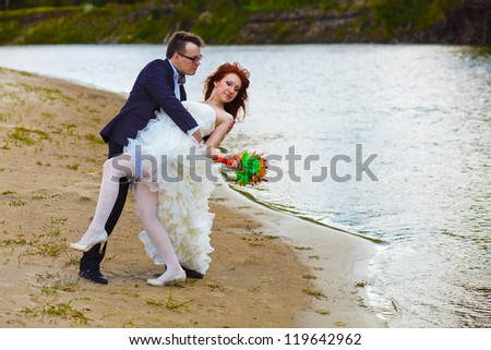newly married couple are on the beach at the river, the bride to the groom bows around the green forest