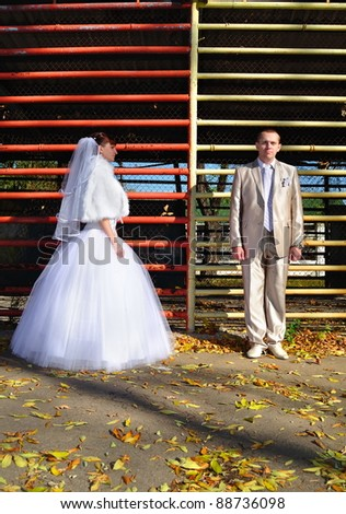 Newly-married couple before a prison lattice