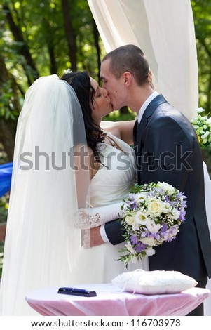 Newly-married couple kiss after ceremony of wedding - stock photo