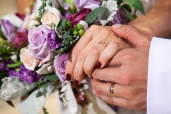Newly married husband gently hold the arm of his wife with wedding bouquet on the background.