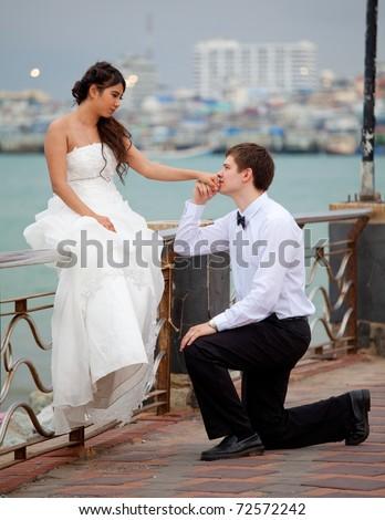 Newly married knee kisses a hand beside the sea