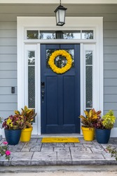 Newly painted Navy Blue front door of new construction grayy home with a vibrant bright and colorful wreath and flower pots and a yello welcome mat