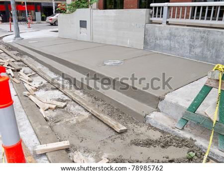 Newly poured cement on urban sidewalk