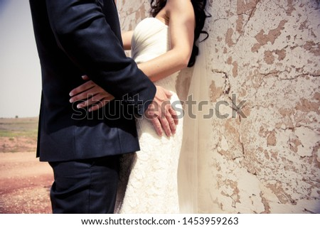 Newly wed couple embraced against a wall. #1453959263