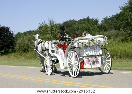 Newly-wed couple in a white, horse-drawn, open carriage