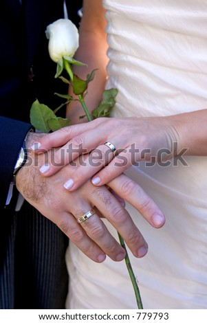 Newly wed couple showing off their gold rings with the woman holding a white rose