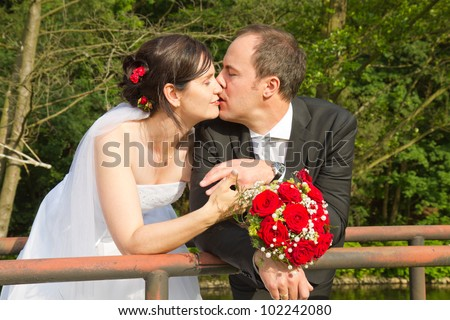 newly wed couple with wedding gown, dark suit and rose bridal bouquet: groom and bride kissing affectionately