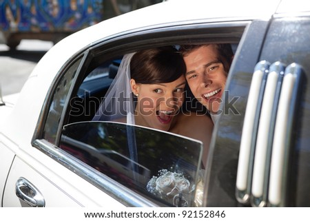 Newly weds laughing in car