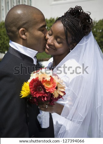 Newlywed african american couple kissing and smiling