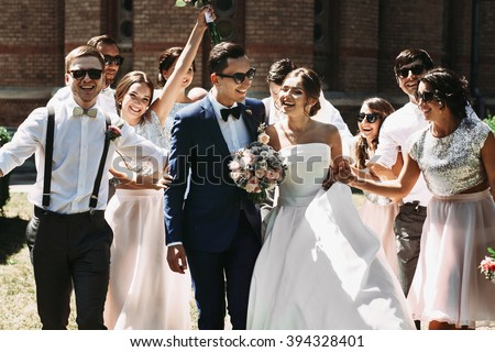 Newlywed couple, bridesmaids & groomsmen having fun outdoors