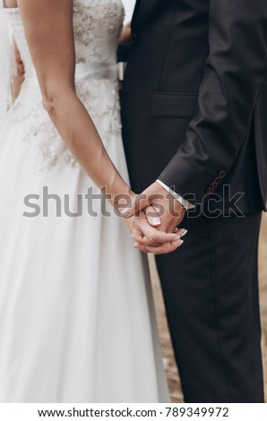 newlywed couple, groom and bride holding each other's hands #789349972