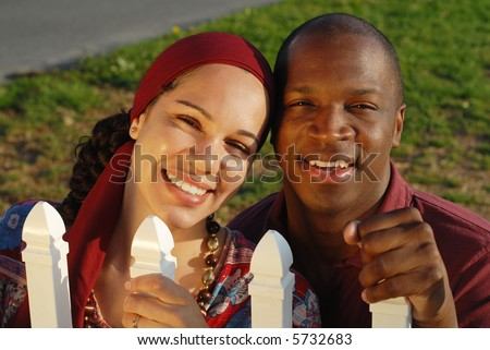 Newlywed couple holding on to a white picket fence, full of dreams and hopes for the life ahead