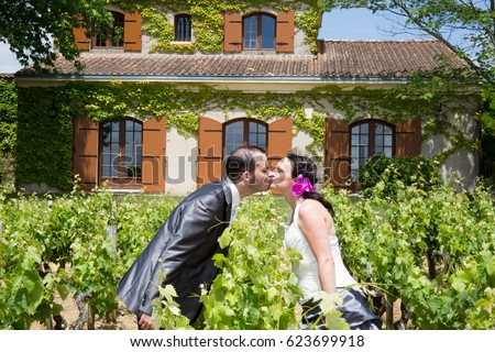 Newlywed couple kiss together outside at the winery