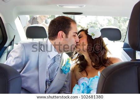 Newlywed couple kissing each other in limousine