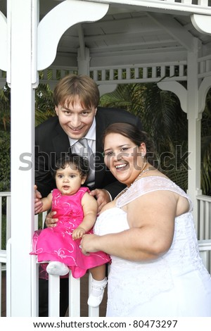 Newlywed couple on their wedding day with their baby girl