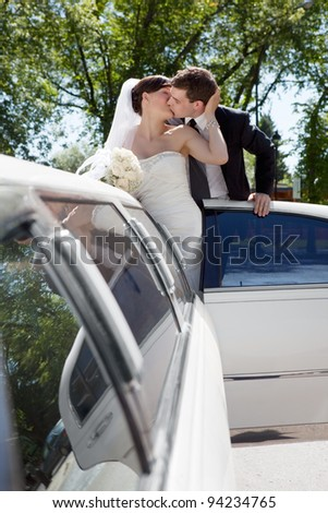 Newlywed Couple Standing Beside Limousine Car Kissing Each Other Holding Bouquet In Hand.