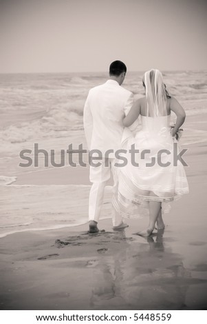 newlywed couple walking arm in arm on the beach, black and white with vignetting