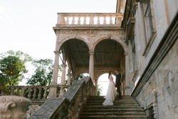 Newlywed standing on the stairs of the old palace and holding each other hands. Bride and groom. Wedding couple. High quality photo