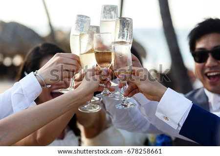 Newlyweds and friends clang their glasses standing outside #678258661