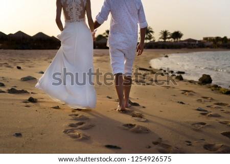 Newlyweds are walking along the beach at sunset
