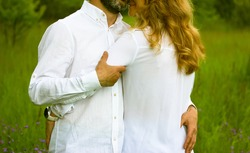 Newlyweds. Beautiful couple in love gently embracing standing in a green meadow in summer. Husband and wife in white shirts showing their feelings for each other. Devotion, purity, harmony, love theme