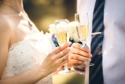 Newlyweds clinking glasses and enjoying romantic moment together at