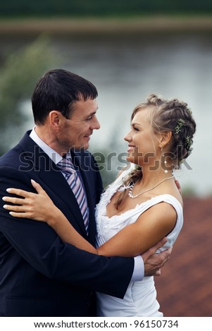 Newlyweds embraces outdoors. River on the background