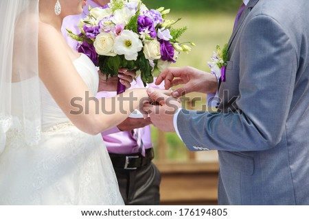 newlyweds holding hands Bride is holding in her hand a beautiful bouquet