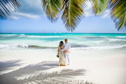 Newlyweds holding hands hugging at white sandy tropical caribbean beach landscape after wedding ceremony of marriage on destination wedding honeymoon travel looking on blue sea in Punta Cana Dominican