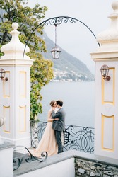 Newlyweds hug and almost kiss under an old arch against the backdrop of Lake Como. Side view