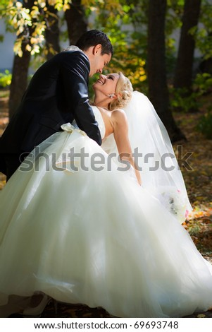 Newlyweds in autumn park, the groom holds the bride leaning for support.
