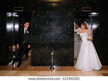Newlyweds in hotel near elevators
