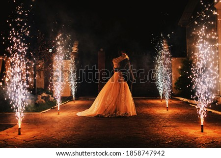Newlyweds kiss on the background of a pyrotechnic show, fireworks fountains Stock photo ©