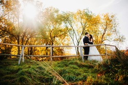 Newlyweds kissing on the background of the autumn forest.