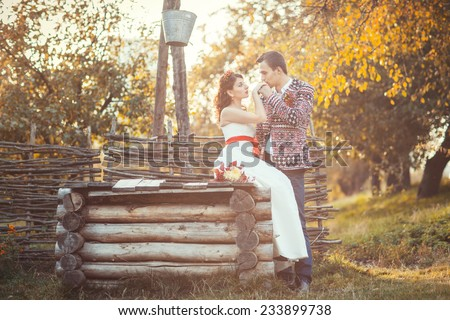Newlyweds near the wooden well, the groom kisses the bride\'s hand