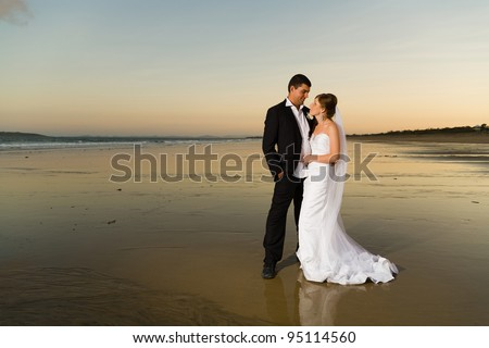 Newlyweds on a deserted beach at sunset with orange tones