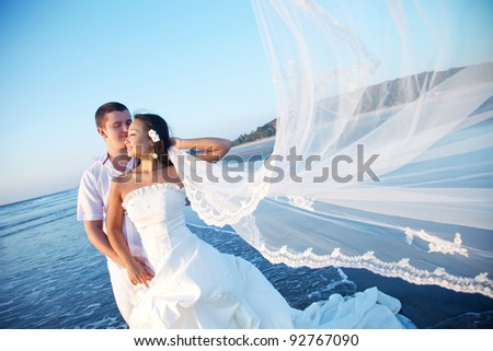 Newlyweds on the beach at sunset