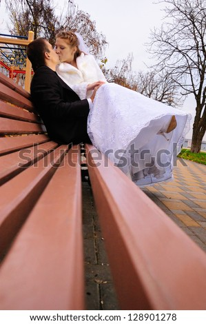 Newlyweds sit on a bench and kiss