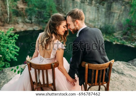 Newlyweds sitting at the edge of the canyon and couple looking each other with tenderness and love. Bride and groom touching foreheads. Back view portrait. Wedding