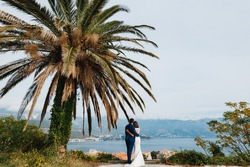 Newlyweds stand hugging each other under a green palm tree against the backdrop of the sea and mountains. Back view