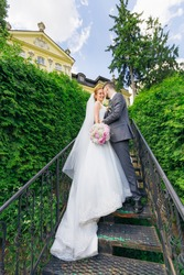 Newlyweds stand on the stairs of the old palace, surrounded by green leaves. The bride and groom hug.