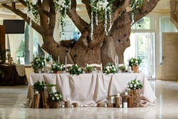Newlyweds table setting decorated in rustic style. Wedding decor with flowers, candles, succulents, greenery and wooden elements. Nature theme in decoration